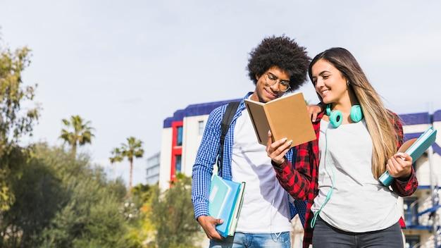 Vista panorámica de una pareja adolescente diversa leyendo el libro fuera del campus