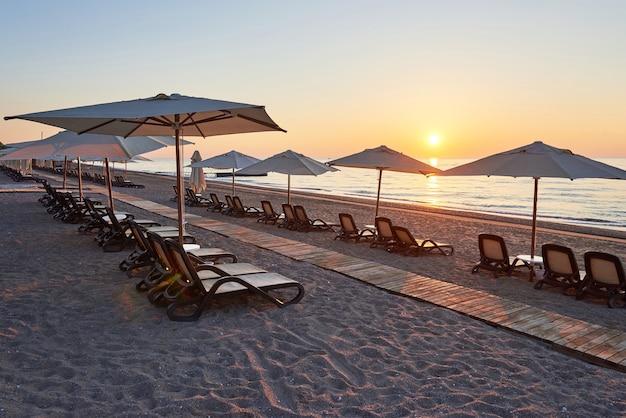 Vista panorámica de la playa de arena en la playa con hamacas y sombrillas abiertas contra el mar y las montañas. hotel. recurso. tekirova-kemer. pavo