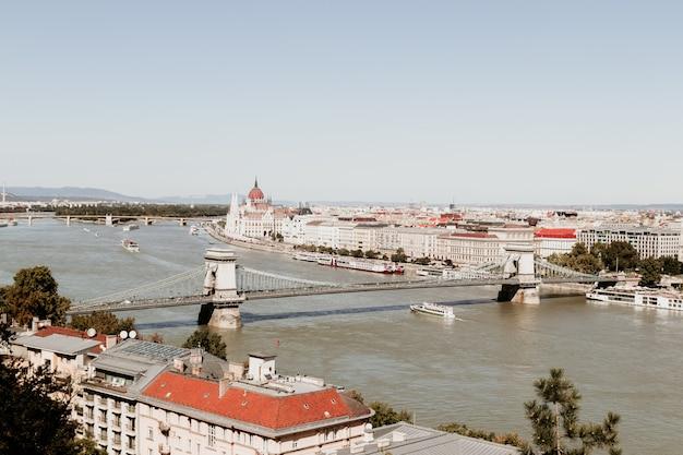 Vista panorámica del puente de las cadenas con figuras de leones y panorama de la ciudad de budapest