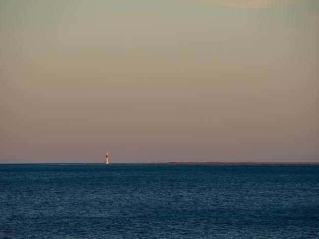 Vista panorámica de una puesta de sol en el mar en calma con un faro rojo y blanco en la distancia espacio de copia