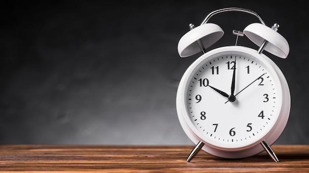 Vista panorámica del reloj de alarma blanco en el escritorio de madera contra el fondo gris