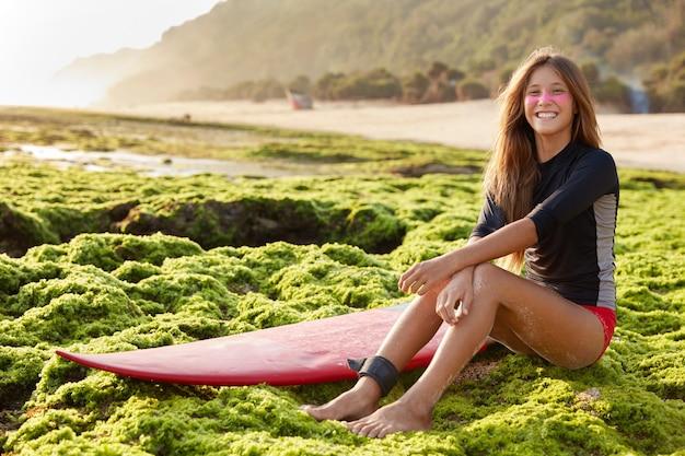 Vista panorámica de la surfista femenina bastante sonriente se siente segura como usa la correa de la tabla de surf