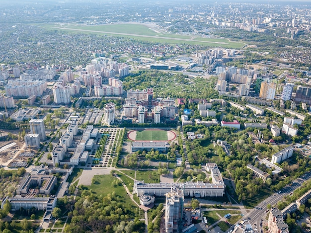La vista panorámica a vista de pájaro desde el dron hasta el moderno distrito de la ciudad con infraestructura urbana y edificios residenciales y el aeropuerto internacional de kiev zhuliany, ucrania, al atardecer de verano.