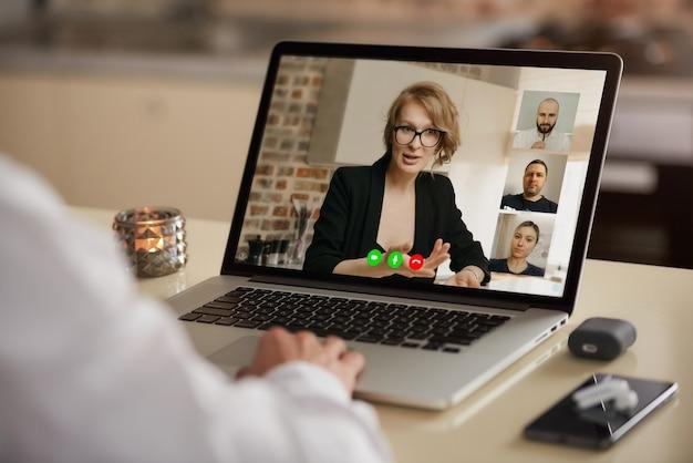 Vista de la pantalla de una computadora portátil de la aplicación de telecomunicaciones durante una reunión en línea sobre el hombro de un hombre.