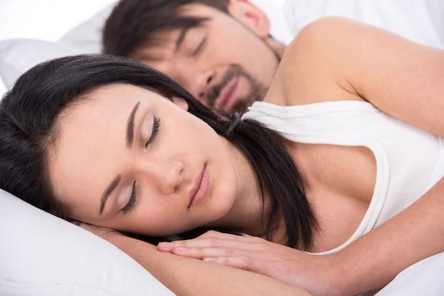 La vista de un par feliz joven está durmiendo en cama.