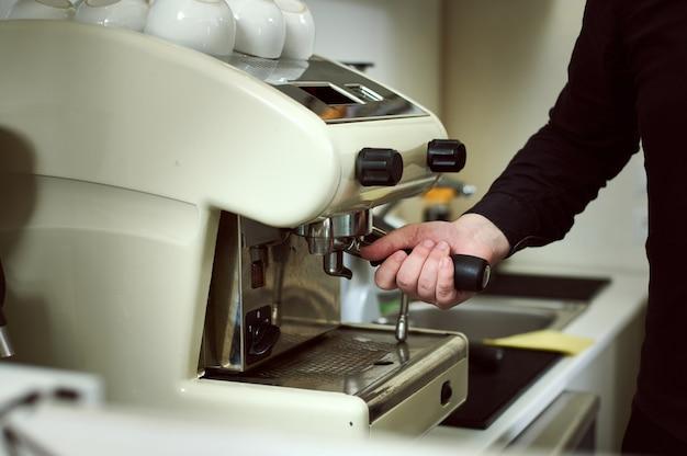 Vista parcial del barista moliendo café y haciendo espresso en una máquina de café profesional