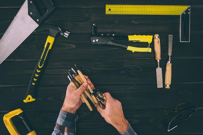 Vista parcial de carpintero con cinceles con varias herramientas industriales alrededor