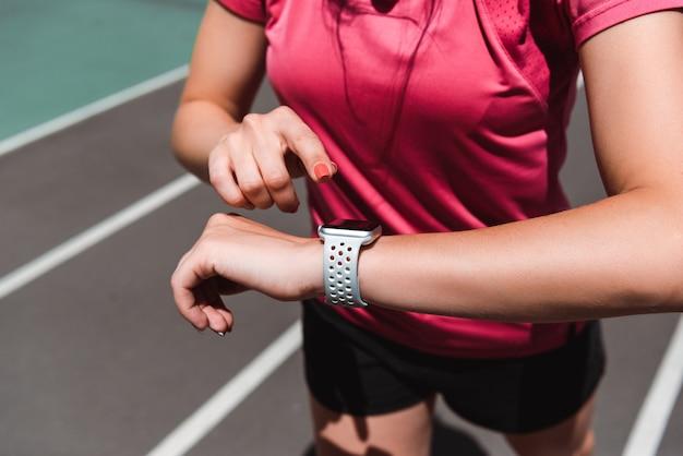 Vista parcial de la deportista mirando el reloj inteligente mientras trota en la pista de atletismo