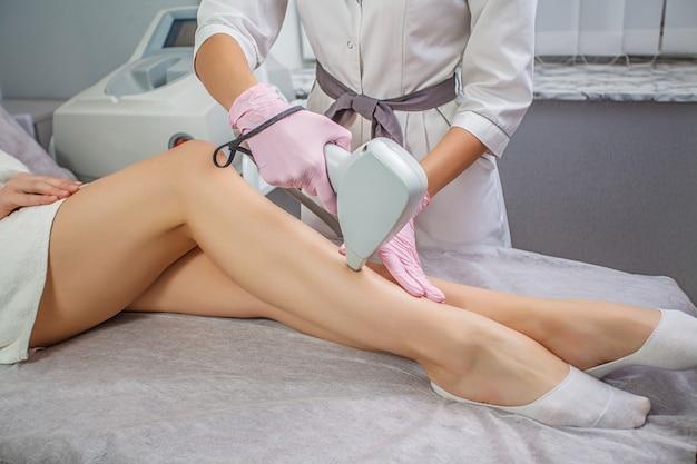 Vista parcial de una mujer joven que recibe depilación láser con depilación en el muslo