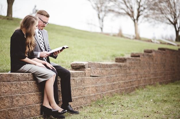 Vista de una pareja vistiendo ropa formal mientras leen un libro juntos en un jardín.