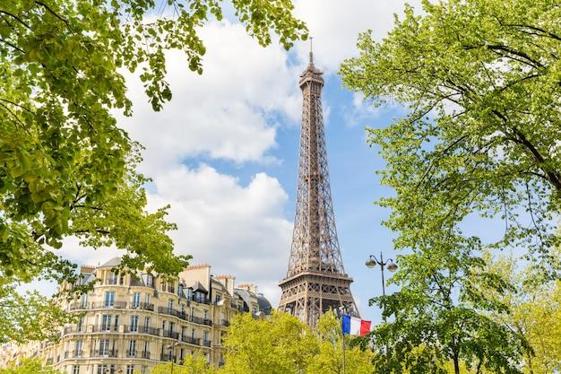 Vista de parís con la torre eiffel y una bandera francesa.