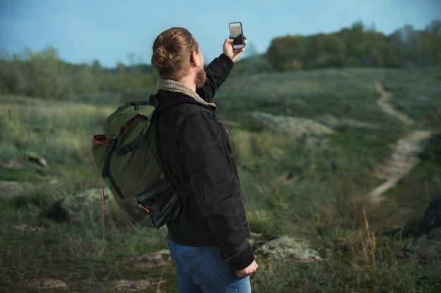 Vista desde la parte de atrás de un excursionista con mochila en busca de señal en un teléfono inteligente permaneciendo en una pasarela en las montañas