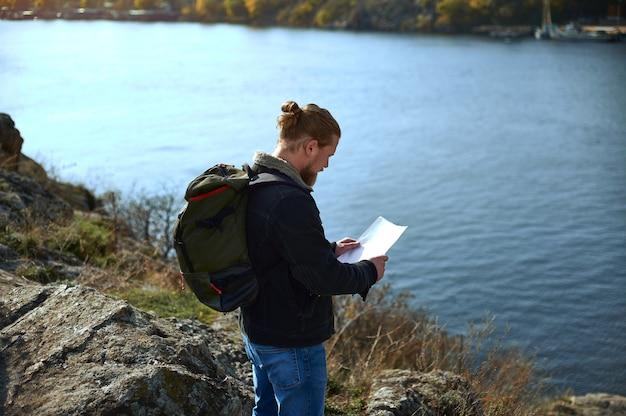Vista desde la parte de atrás de un viajero hombre con mochila mirando el mapa de ruta en el borde del acantilado