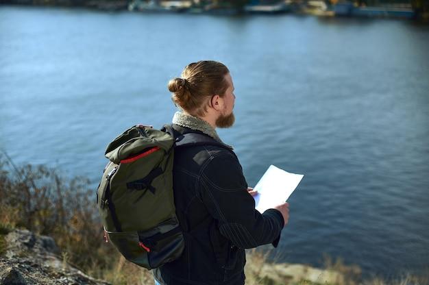 Vista desde la parte de atrás de un viajero hombre con mochila sosteniendo un mapa de ruta en el borde del acantilado y admirando la belleza de la naturaleza