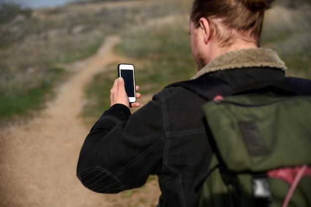 Vista desde la parte posterior de un hombre aventurero de senderismo con brújula en el teléfono inteligente. concepto de personas que viajan en la naturaleza.