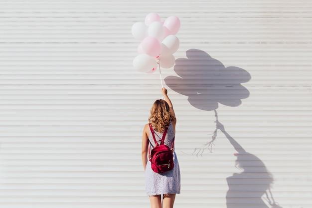 Vista desde la parte posterior de la mujer joven con mochila, sosteniendo globos de aire