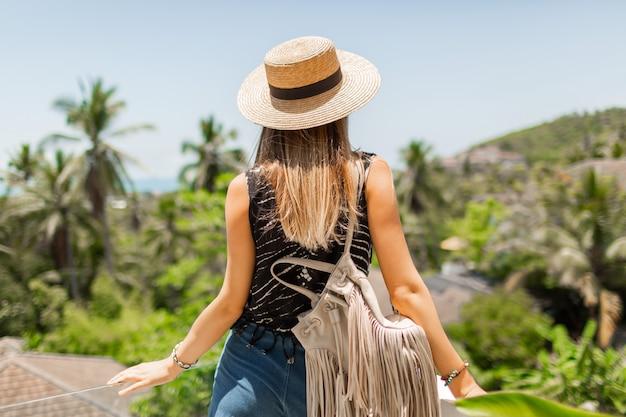 Vista desde la parte posterior de la mujer viajera con sombrero de paja disfrutando del increíble paisaje tropical