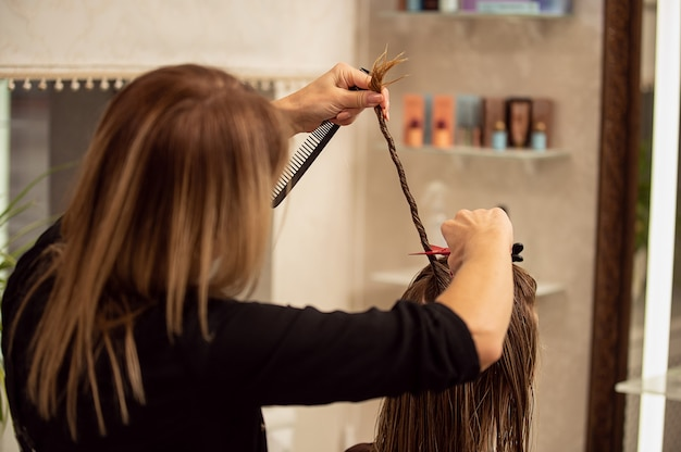 Vista de la parte posterior de la peluquería recortando el cabello largo rubio con tijeras en peluquería