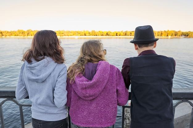 Vista desde la parte posterior de tres amigos adolescentes niño y dos niñas