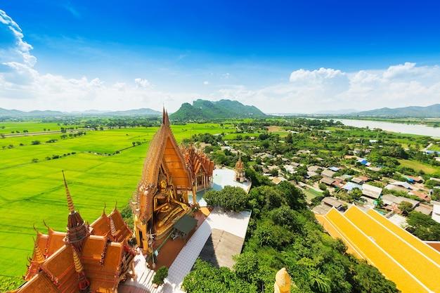 Una vista desde la parte superior de la pagoda, estatua dorada de buda con campos de arroz y montaña, wat tham sua (
