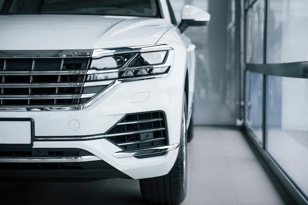 Vista de partículas del coche blanco de lujo moderno estacionado en el interior durante el día