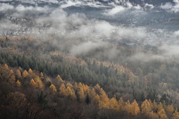 Vista de un pequeño pueblo entre las montañas rodeado por un paisaje de niebla