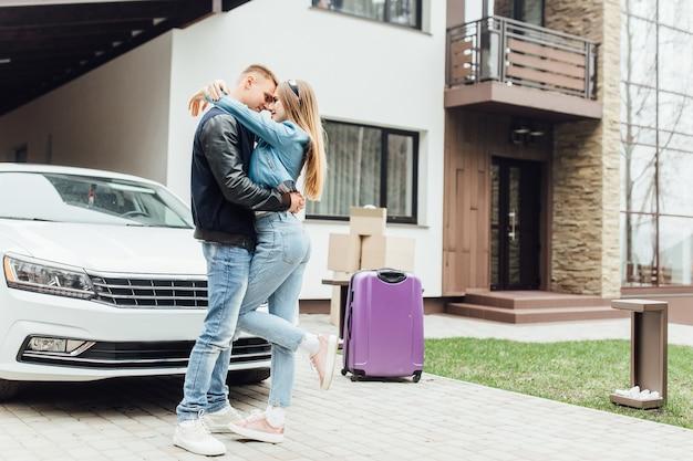 La vista perfecta de la familia feliz está de pie cerca de su casa moderna y abrazándose.