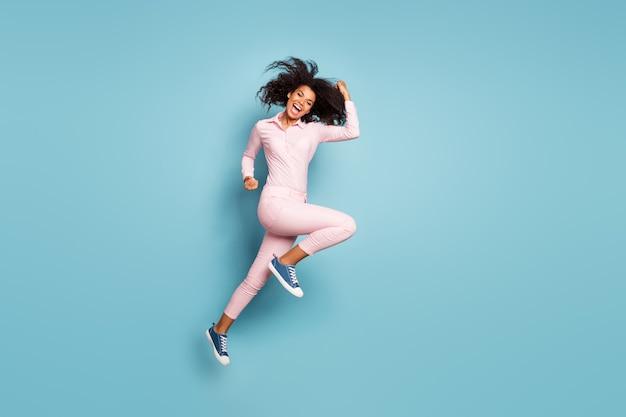 Vista de perfil de cuerpo completo de la encantadora dama saltando alto celebrar la victoria