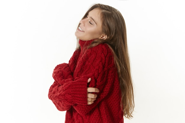 Vista de perfil de la hermosa joven de pelo largo manteniendo los ojos cerrados y abrazándose a sí misma, sonriendo con alegría y satisfacción, expresando su amor propio, vestida con un acogedor jersey marrón. estilo y moda