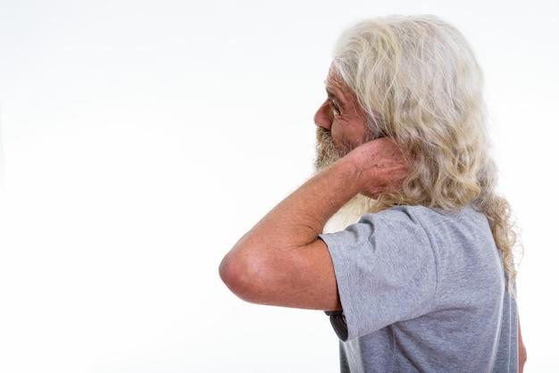 Vista de perfil del hombre barbudo senior estresado que tiene dolor
