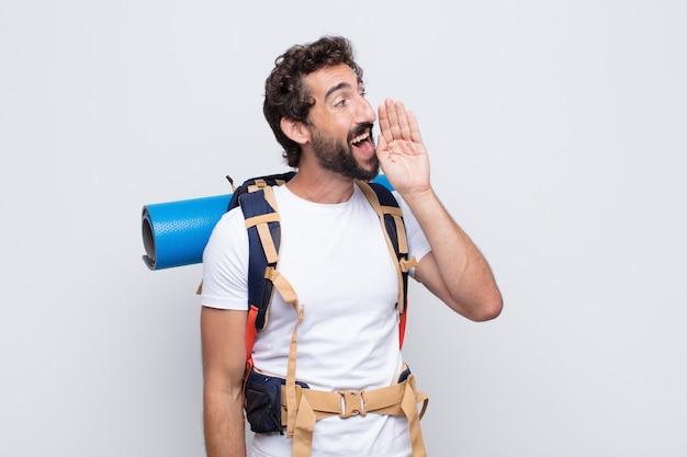 Vista de perfil de hombre joven, luciendo feliz y emocionado, gritando y llamando para copiar espacio en el lateral