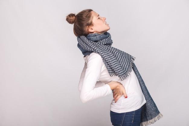 Vista de perfil mujer enferma que duele la espalda o los riñones. tiro de interior