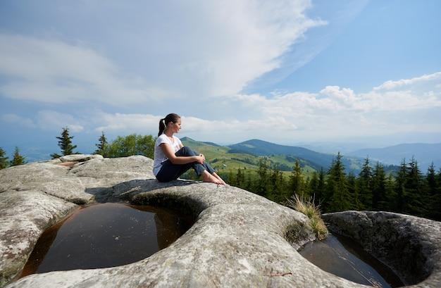 Vista de perfil de niña turista sentado en una enorme roca con gran charco en el medio bajo un hermoso cielo nublado