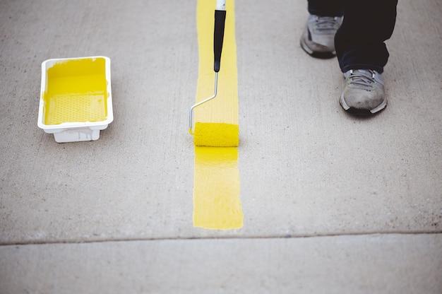Vista de una persona repintando las líneas de estacionamiento del asfalto de un estacionamiento con pintura amarilla