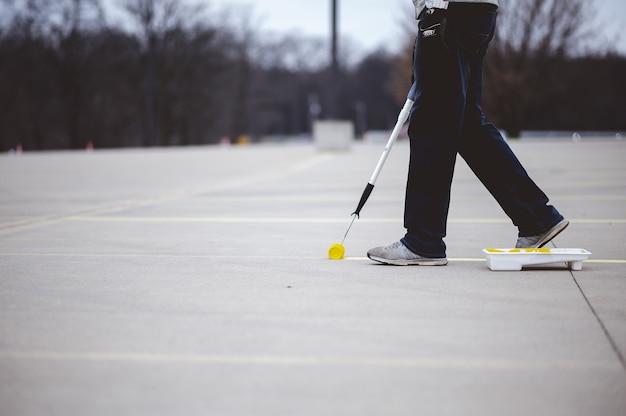 Vista de una persona repintando las líneas de estacionamiento sobre el asfalto de un estacionamiento con pintura amarilla