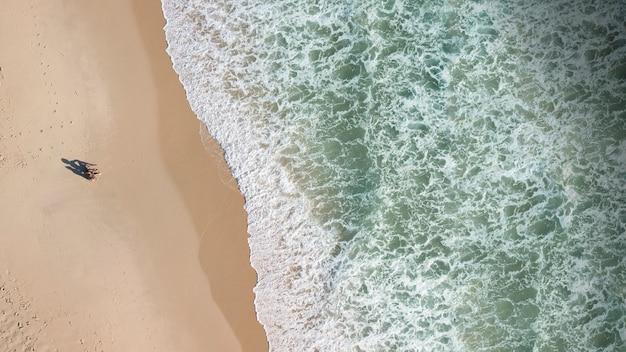 Vista de personas en la costa y olas de espuma.