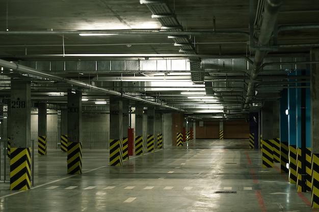 Vista en perspectiva del interior de la zona de aparcamiento vacía con filas de columnas y marcas y sin coches alrededor