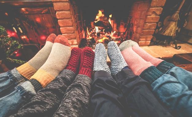 Vista de las piernas de la familia feliz acostada junto a la próxima chimenea