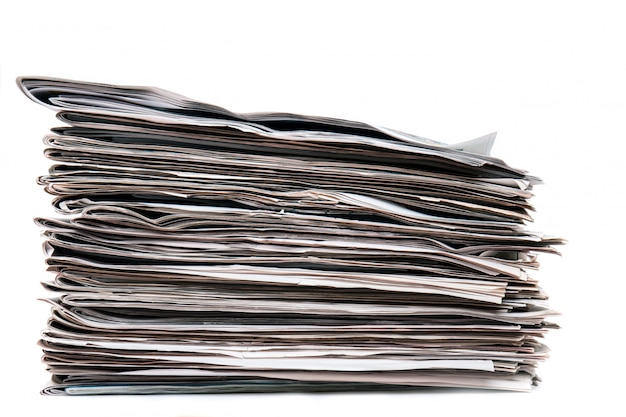 Vista de una pila de periódicos apilados aislados en un fondo blanco.