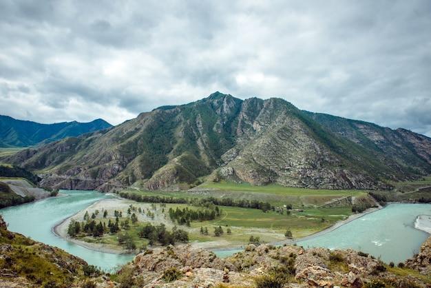 Vista pintoresca sobre la confluencia de dos ríos de montaña. el río katun y el río chuya contra las montañas de altai, rusia. paisaje de montaña en un día nublado de verano