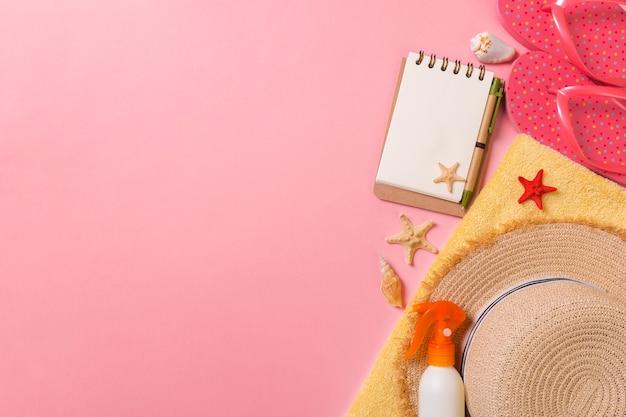 Vista plana endecha, superior concepto de viaje. accesorios de verano con papel de nota y concha sobre fondo rosa.