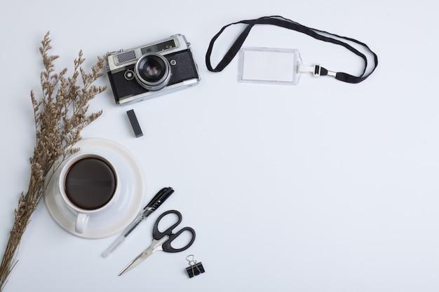 Vista plana endecha, vista superior mesa de oficina moderna. cámara, café y bolígrafo con etiqueta de flor seca sobre fondo blanco.
