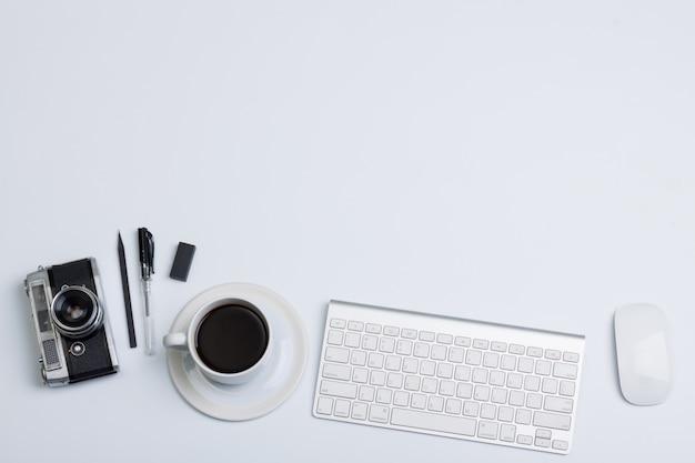 Vista plana endecha, vista superior mesa de oficina moderna. cámara café y teclado mouse sobre fondo blanco.