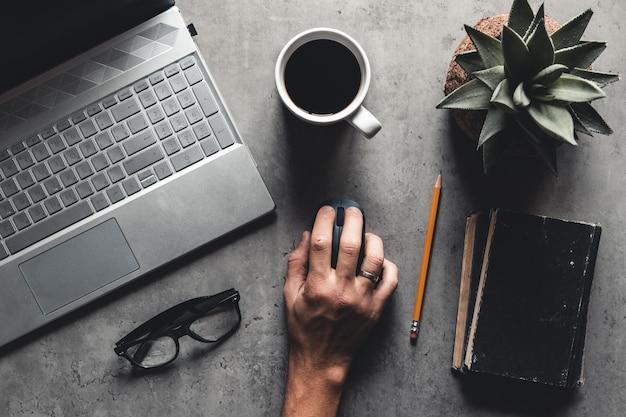 La vista plana del escritorio de oficina con computadora portátil, mouse, árbol, clip de papel, taza de café, cuaderno, lápiz, gafas negras sobre fondo blanco.