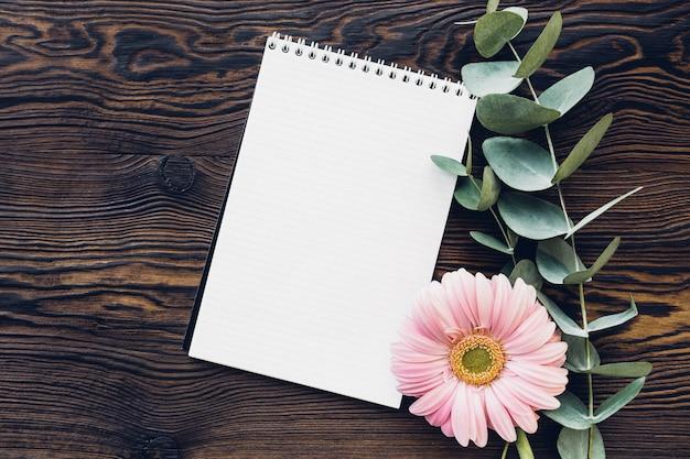 Vista plana de flores rosas y diario sobre madera, vista desde arriba. bosquejo