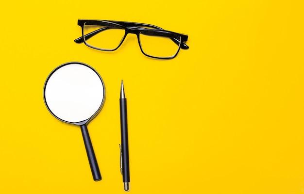 Vista plana o superior con un bolígrafo negro, lupa y una calculadora sobre un fondo amarillo brillante con espacio de copia vacío