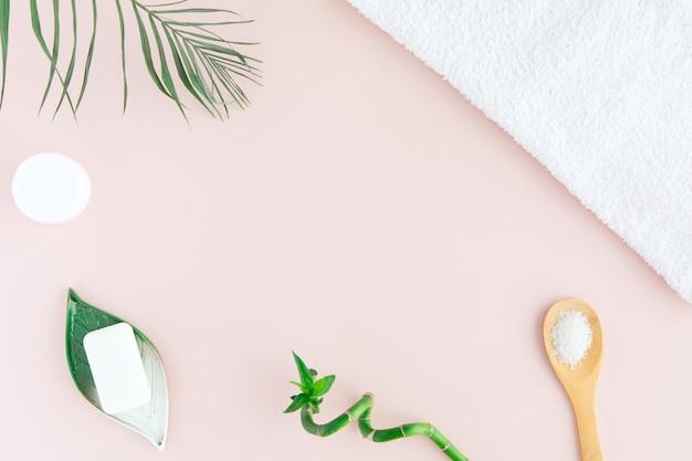 Vista plana y superior de una toalla blanca, tarro de crema, hojas de palma verde y bambú en rosa pastel