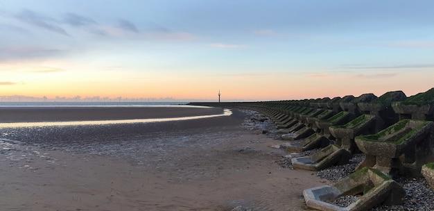 Vista de la playa en liverpool al atardecer, filas de rompeolas, reino unido