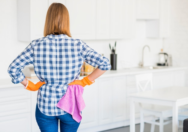 Vista posterior del ama de llaves femenina en guantes anaranjados que sostienen la servilleta rosada en la cocina