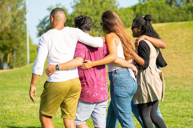 Vista posterior de amigos abrazándose mientras pasea por la pradera. jóvenes hablando mientras caminan juntos. concepto de amistad